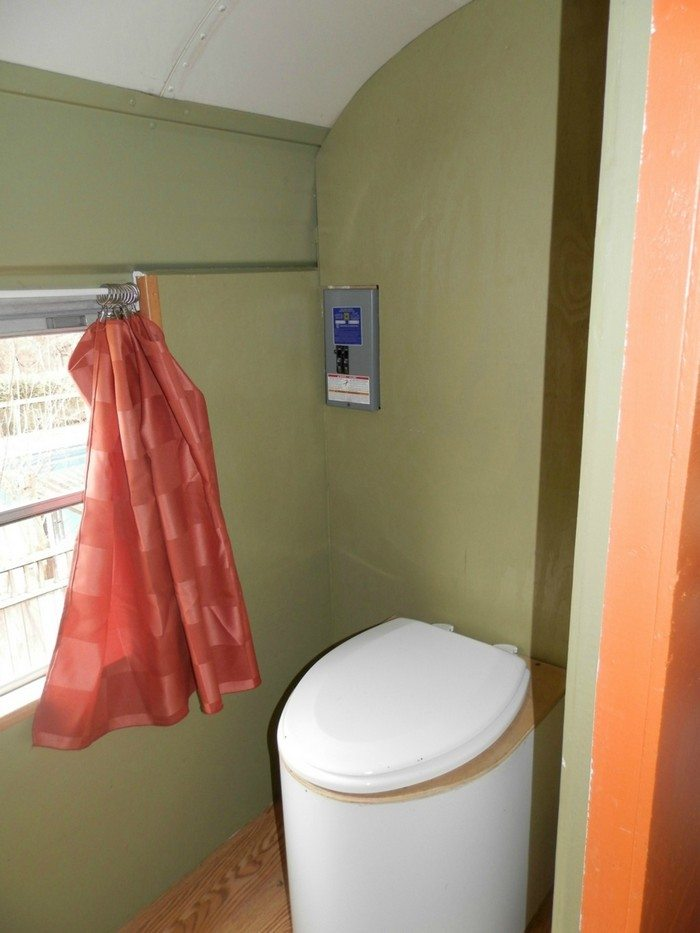 Before: The bus came with a waterless toilet, set in against walls in olive green.