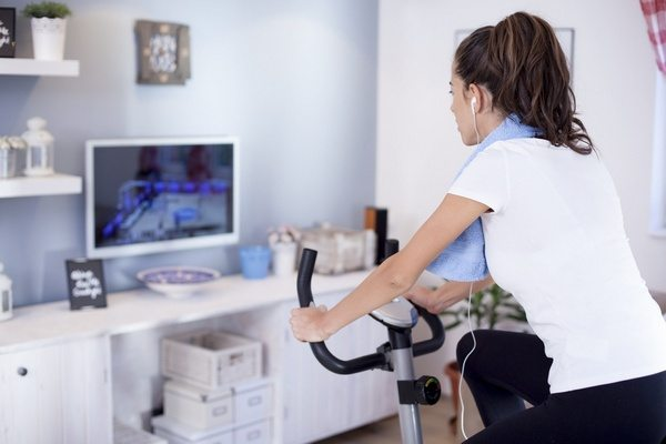 Young sporty woman training on exercise bike in the living room and watching tv