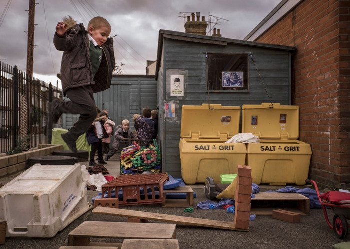 A boy about to send a pile of bricks flying at the risk-enhanced playground at the Richmond Avenue Primary and Nursery School in Shoeburyness, England. Credit Tom Jamieson for The New York Times