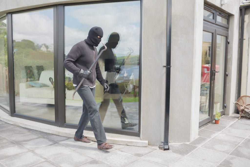 Burglar with crow bar outside home
